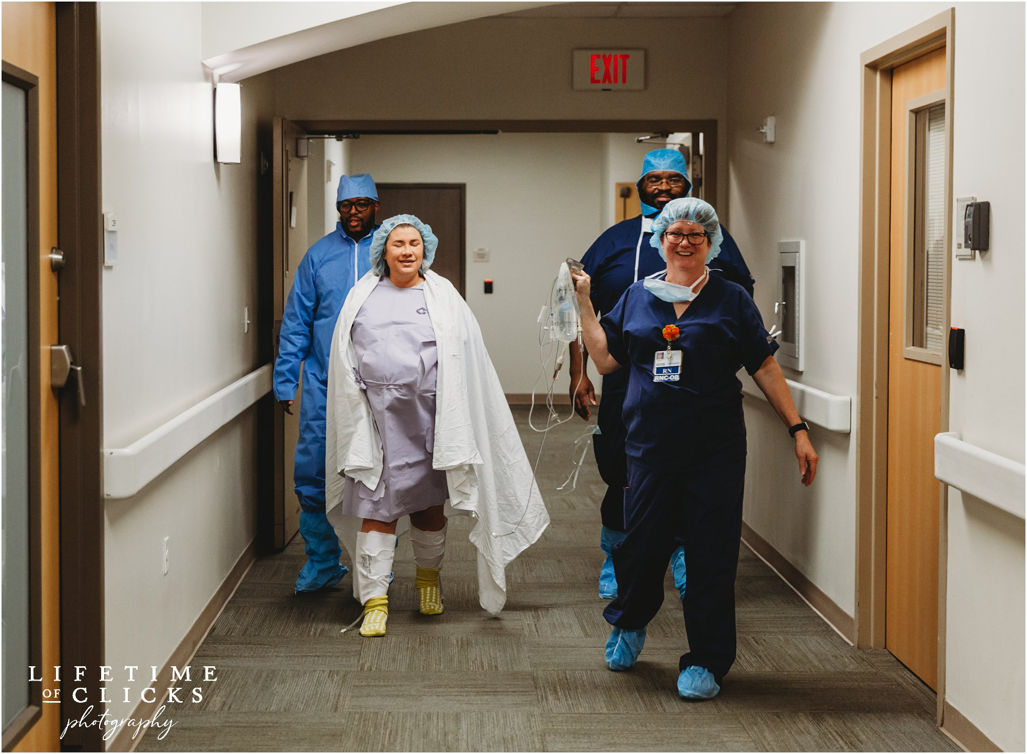 pregnant woman walking with nurses to surgery for c-section